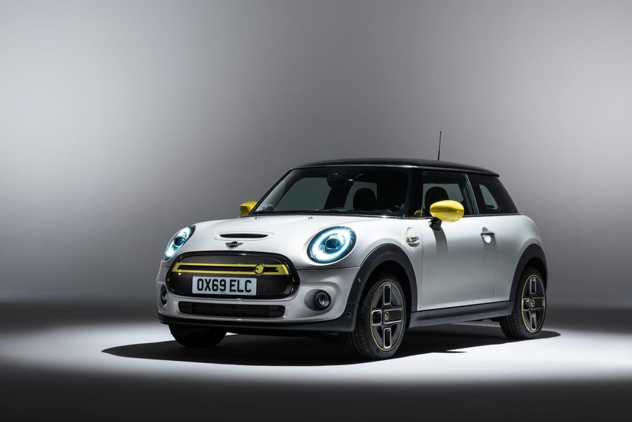 White and yellow Mini Electric parked in a showroom
