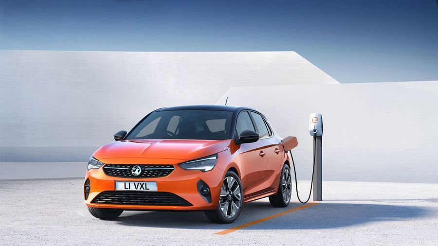 Orange Vauxhall Corsa E electric car charging in a white space