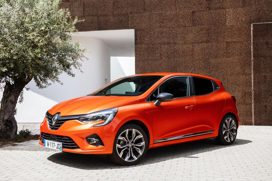 Orange Renault Clio parked in front of a modern house