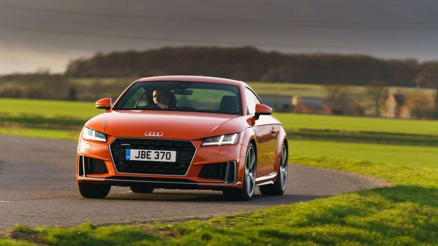 Orange Audi TT coupe driving through fields