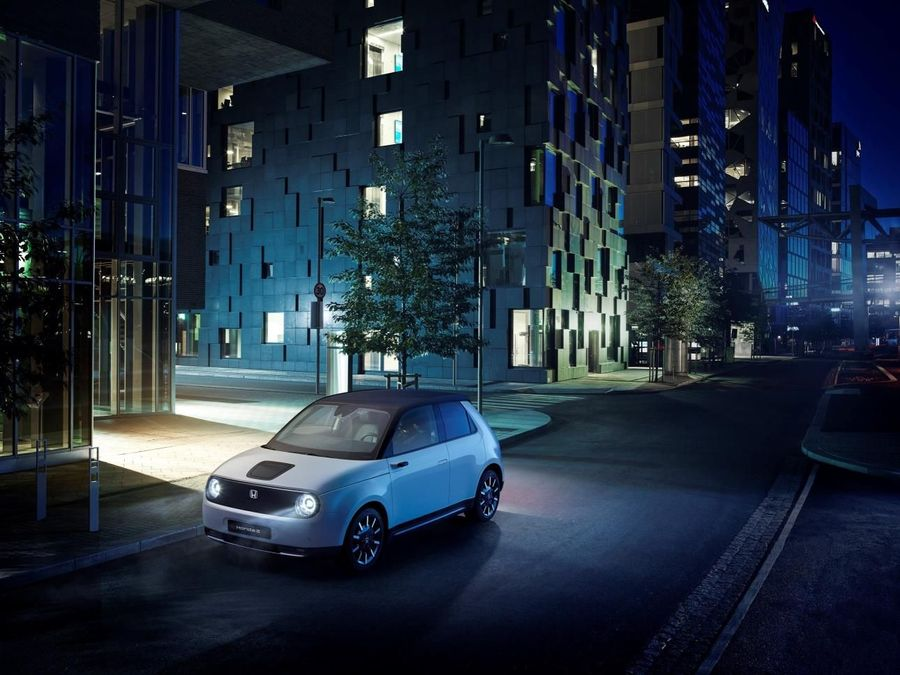 Concept art of a Honda E parked in a blue and green cityscape