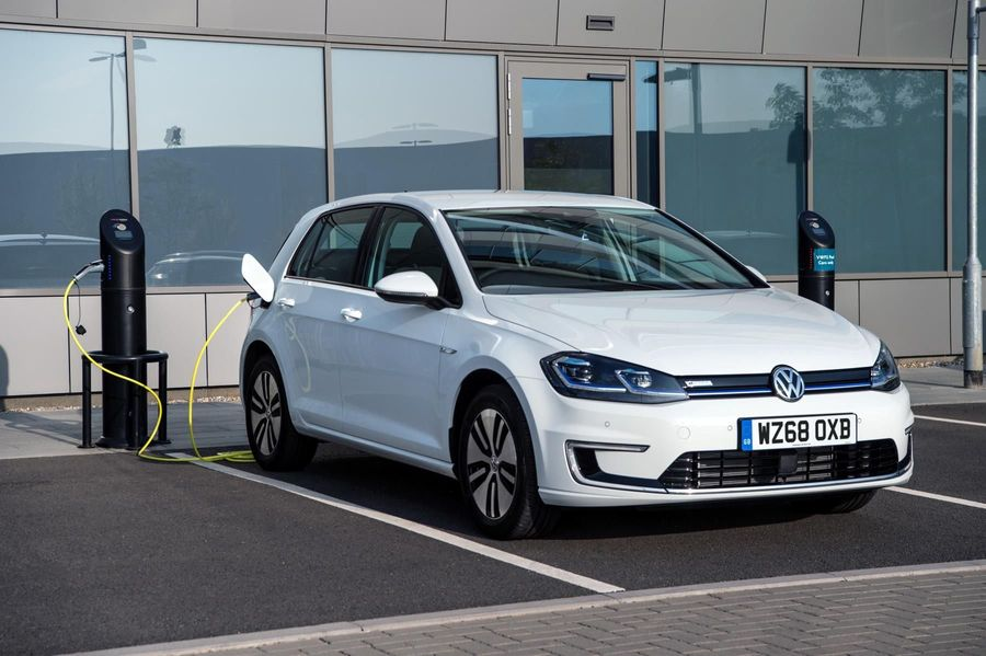 White Volkswagen e-Golf lease electric car charging outside an office